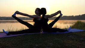 Two Women Sit Back-To-Back on Mat And Raise One Leg Each at Sunset. Two Cheerful Young Women Stretch Out Their Legs While Sitting on Their Mats and Taking the stock footage