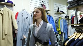 Two cheerful young women are walking through a clothing store. Two girlfriends smiling choose the clothes in the store. They help each other with a choice stock video footage