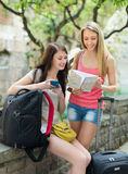 Two cheerfull girls with map. Chasing city streets and looking for hotel Royalty Free Stock Images