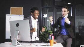 Two Successful businessmans juming and raising hands in the office stock video footage