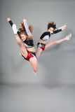 Two Cheerleaders Jumping Stock Photography