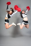Two Cheerleaders Jumping Royalty Free Stock Images