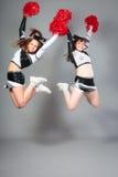 Two Cheerleaders Jumping. Studio shot of two cheerleaders jumping in front of grey background Stock Image