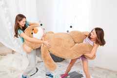 Two cheerul playful sisters playing with big plush bear Royalty Free Stock Photography