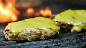 Two cheese cutlets for grilled burgers close up, fire flames in the background, slow motion stock video