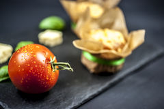 Two cheese muffins, basil, tomato and cheese. On black background Royalty Free Stock Photos