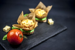 Two cheese muffins, basil, tomato and cheese. On black background Royalty Free Stock Image