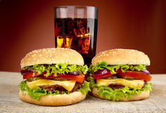 Two cheeseburgers,glass of cola on wooden table on red spotlight Stock Images