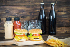 Two cheeseburgers with two bottles of dark beer Royalty Free Stock Photos