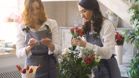 Two chef woman and florist preparing flowers, fruits and vegetables for making fruit bouquet stock video
