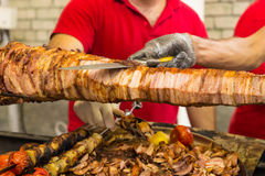 Two chefs carving a spit roast. Over a barbecue fire using a sharp kitchen knife to slice of thin slices for a buffet or takeaway menu Stock Photography