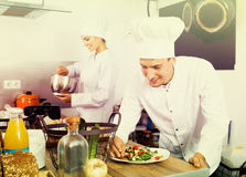 Two chefs cooking food. Two pretty adult men and women chefs cooking food at restaurant`s kitchen Stock Photos