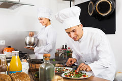 Two chefs cooking food Stock Images