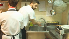 Two chefs cooking in the restaurant kitchen stock video footage