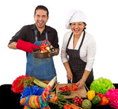 Two chefs preparing for a Mexican celebration. Two attractive happy chefs preparing for a Mexican celebration by cutting vegetables and flipping them on a frying Royalty Free Stock Photo