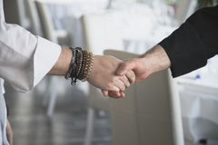 Two chefs shake hands before a culinary competition. Close up view of business partnership handshake concept.Photo of two cooks handshaking process.Successful stock image