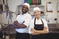 Two chefs standing with arms crossed in the commercial kitchen. Portrait of two chefs standing with arms crossed in the commercial kitchen at restaurant stock photos