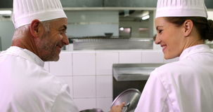 Two chefs talking and smiling at camera. In a commercial kitchen stock video footage