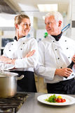 Two chefs in team in hotel or restaurant kitchen. Two chefs - man and woman - in hotel or restaurant kitchen working and cooking in team Royalty Free Stock Images