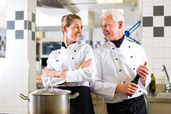Two chefs in team in hotel or restaurant kitchen Royalty Free Stock Photos