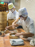 Two chefs in white uniforms preparing a dish of dough in a little kitchen, Singapore Royalty Free Stock Image