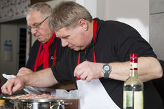 Two chefs at work. Two cooks in black shirts at work Royalty Free Stock Photo