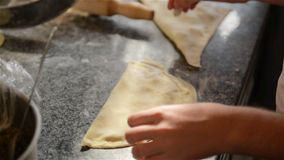 Two chefs work with the dough, cooked pasties in a professional kitchen. HD stock video footage