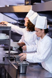 Two chefs working at order station in a kitchen Royalty Free Stock Photo