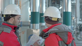 Two chemical factory workers having conversation in plant. Professional shot on BMCC RAW with high dynamic range. You can use it e.g in your commercial video stock video footage