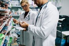 Pharmacists checking inventory at pharmacy. Two chemist working in pharmacy drugstore. Male and female pharmacists checking inventory at pharmacy Royalty Free Stock Photography