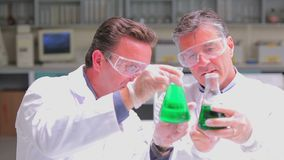Two chemists experimenting with the green liquid in beakers. In the laboratory stock video footage