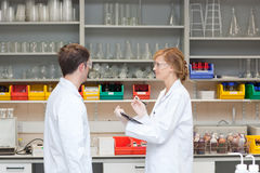 Two chemists in their laboratory. Talking about tests Stock Image