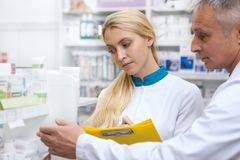 Two chemists working at drugstore together stock image