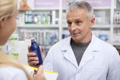 Two chemists working at drugstore together. Senior male pharmacist handing medication to his female colleague. Two chemists working together at the drugstore royalty free stock image