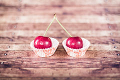 Two cherries on cupcake liners Stock Photos