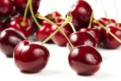 Two cherries in front of many. On white background royalty free stock photos