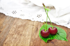 Two cherries with leaves Stock Photo