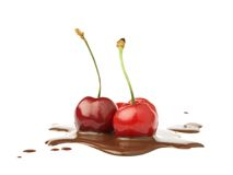 Two cherries on liquid chocolate Stock Photos