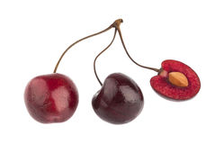 Two cherries and one cut in half Stock Photos
