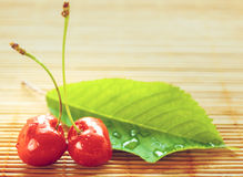Two cherries placed near green leaf on bamboo tablecloth Stock Photos