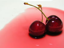 Two cherries on a white plate. Two cherries in red sauce on a white plate stock images
