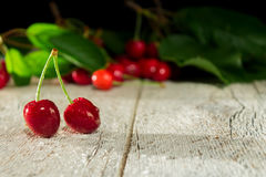 Two cherries on a wooden blurred background Stock Photography