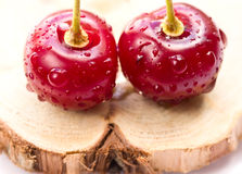 Two cherries on a wooden board Royalty Free Stock Photo
