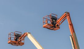 Two Cherry Picker Machines. Against a blue sky stock image