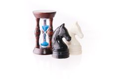Two chess horses with sand-clock Stock Photography