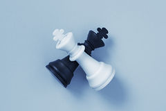 Two chess kings lying on a light blue background Stock Images