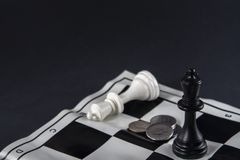 Two chess kings standing in front of each other, coins between t royalty free stock image