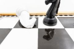Two chess knights with the vanquished white chess piece lying on its side and the black knight standing upright signifying success. There is a white background stock photo