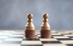 Equal gender pay. Two chess pawns with gender symbols on top of a heap of coins stock images