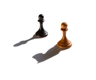 Two chess pawns one casting a knight piece shadow Royalty Free Stock Photo